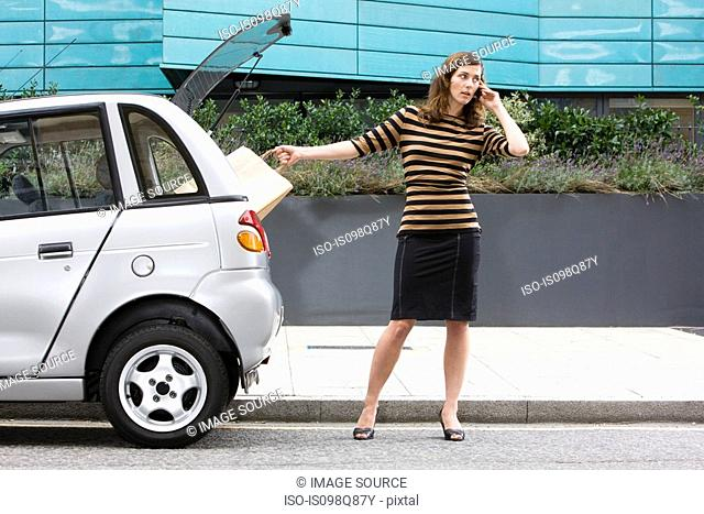 Woman on cellphone by car