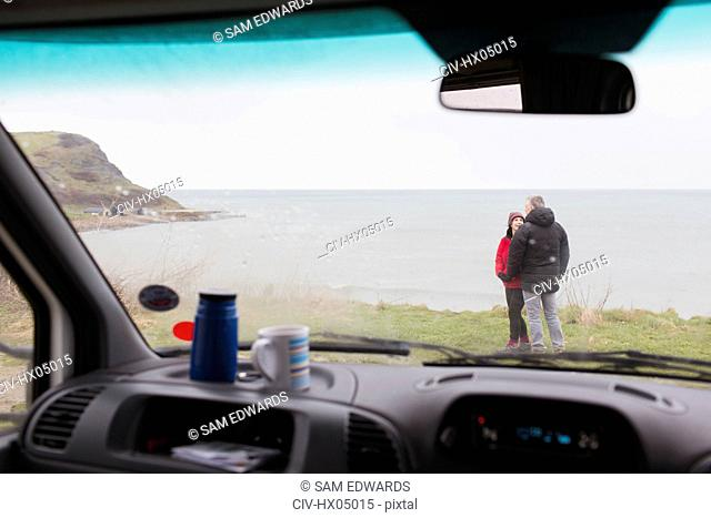 Couple talking outside motor home on cliff overlooking ocean