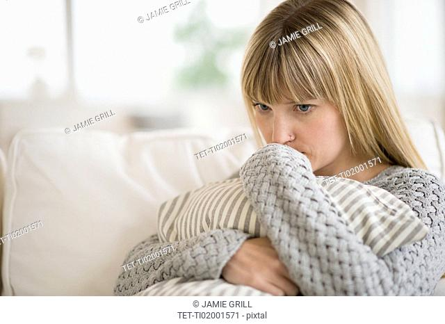Woman sitting on sofa and thinking