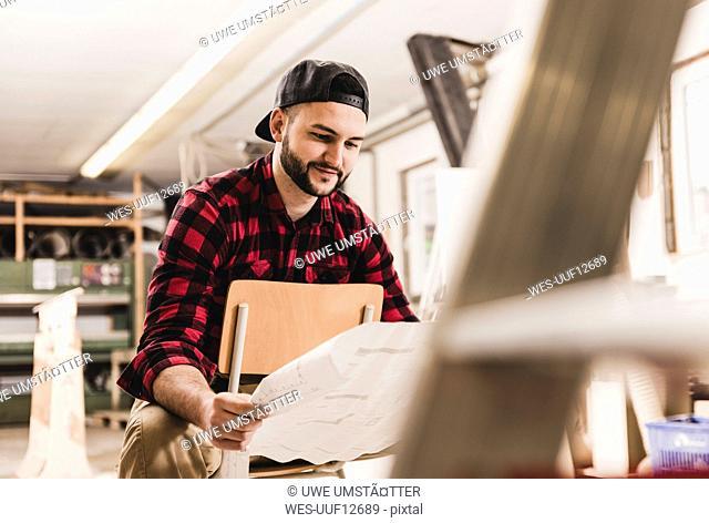 Worker looking at draft in workshop