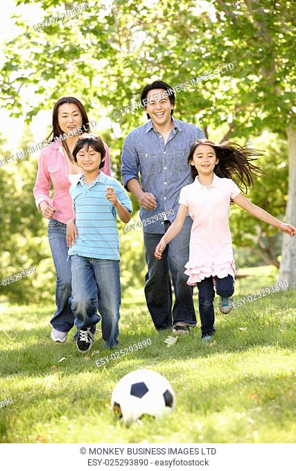 Asian family playing soccerl in park