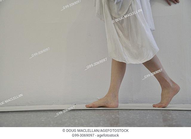 A side view from the waist down of a woman artist in a flowing white dress as she creates a performance art work at an artist run gallery in Windsor, Canada