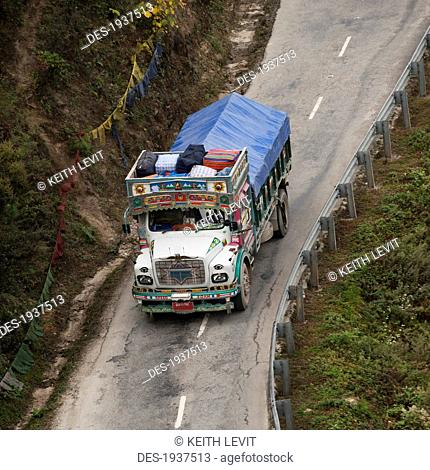 a truck covered with a tarp traveling on a road, thimphu district bhutan