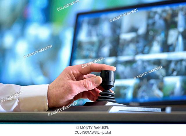 Close up of hand on camera control joystick in control room with video wall