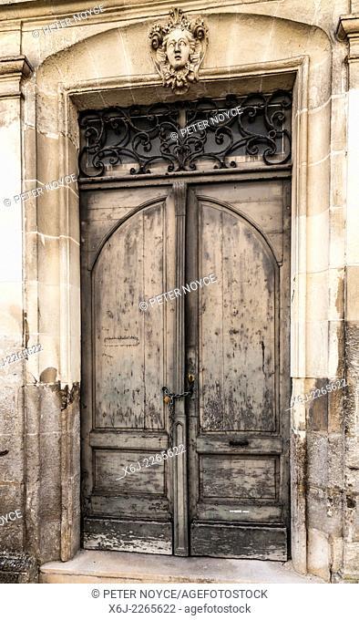 Old characterful french door with overdoor sculpture of woman's head
