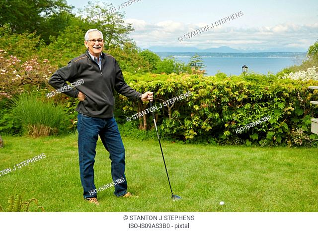 Portrait of senior man, holding golf club