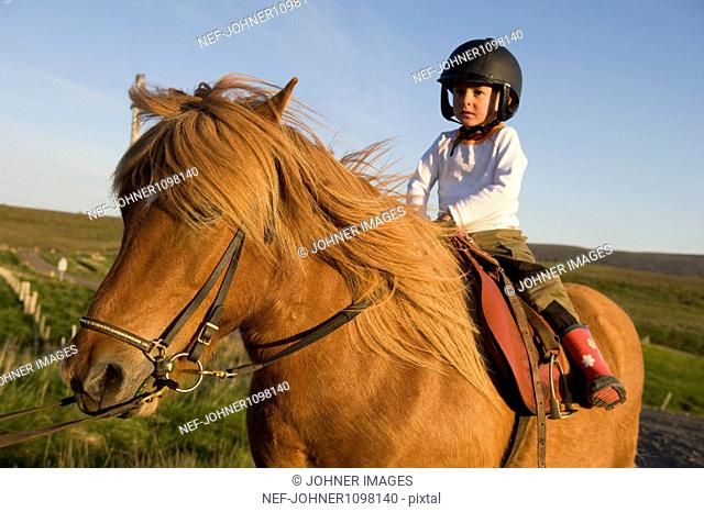 Boy wearing helmet and riding horse