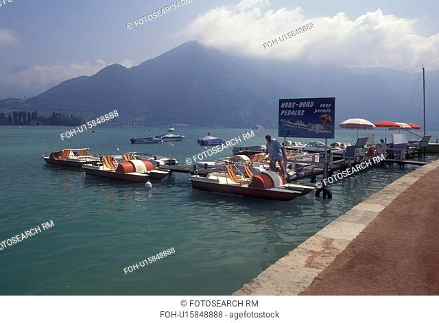 Annecy, France, Haute-Savoie, Rhone-Alpes, Europe, Paddleboats docked on the waterfront of Lake Annecy (Lac d' Annecy) surrounded by mountains in Annecy