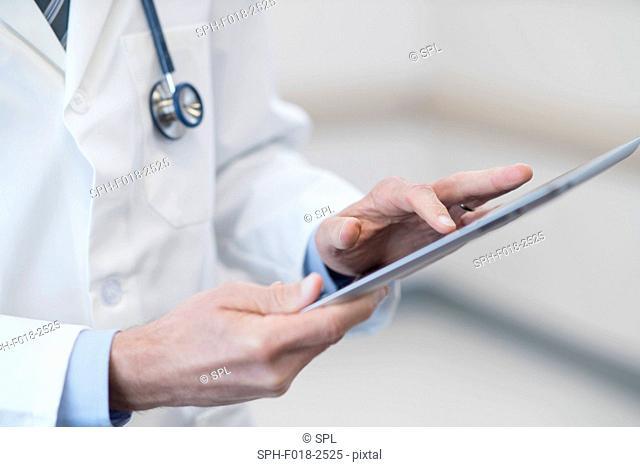 Male doctor using digital tablet