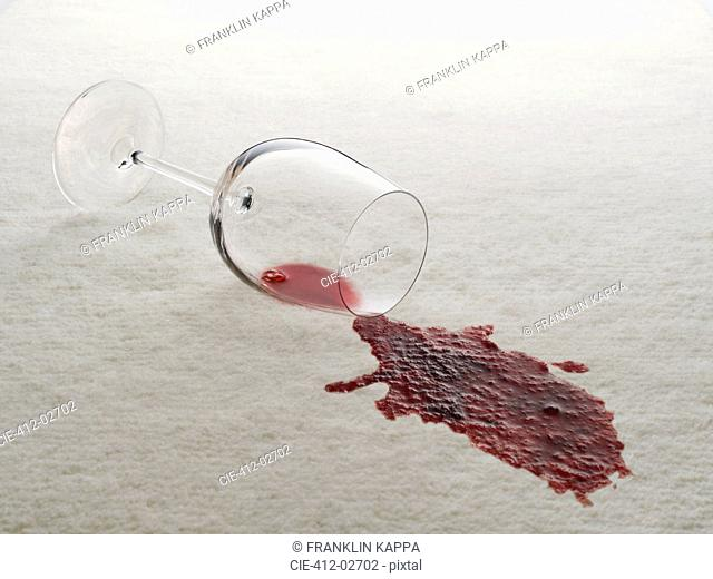 Glass of red wine spilled on white carpet