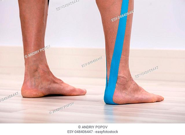 Low Section Of A Man Therapeutic Tape On His Leg