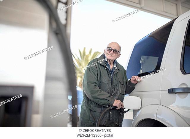 Elderly man fueling car at gas station
