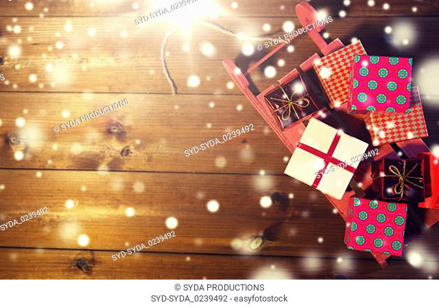 close up of christmas gift boxes on wooden sleigh