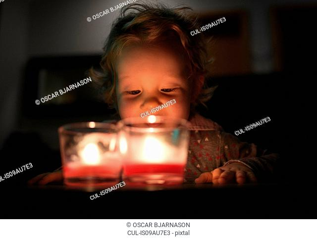 Surface level view of preschool girl looking down at burning candles