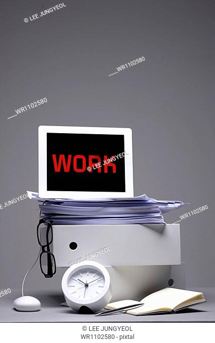 a laptop saying work on a pile of papers