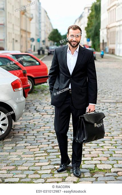 Stylish businessman walking to work across a cobbled parking lot carrying his briefcase smiling at the camera