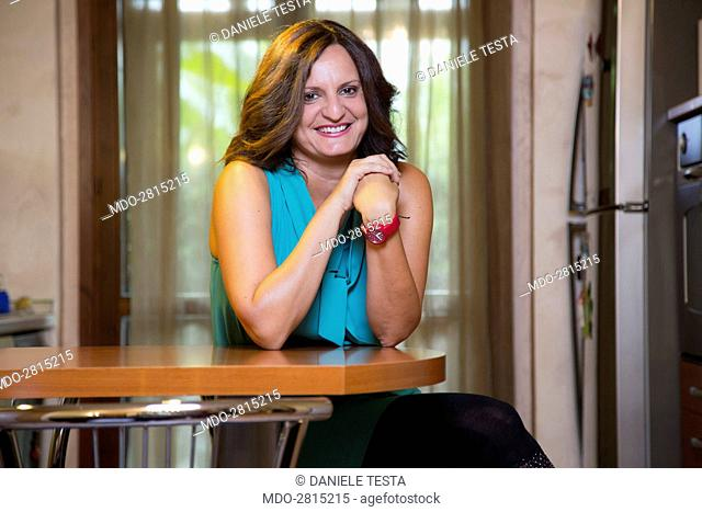 Smiling woman sitting at the table in the kitchen. Treviglio (Italy), 19th December 2014