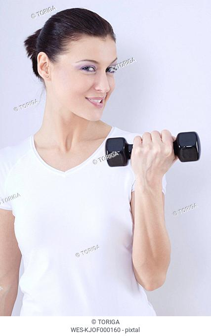 Close up of mid adult woman with barbells against white background, smiling, portrait