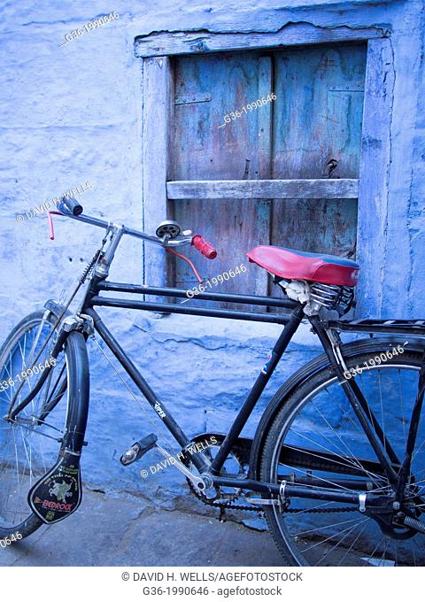 Bicycle parked in front of blue painted wall in Jodhpur, Rajasthan, India
