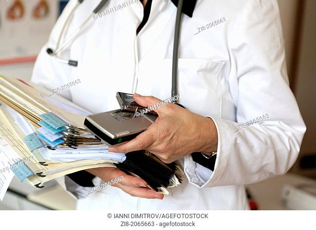 Close-up of overworked doctor holding patient files