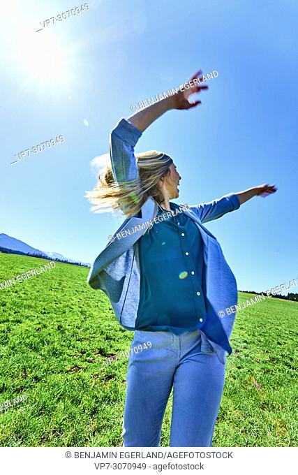 Vibrant woman enjoying sunny weather, at countryside, full of energy. Waakirchen, Bavaria, Germany
