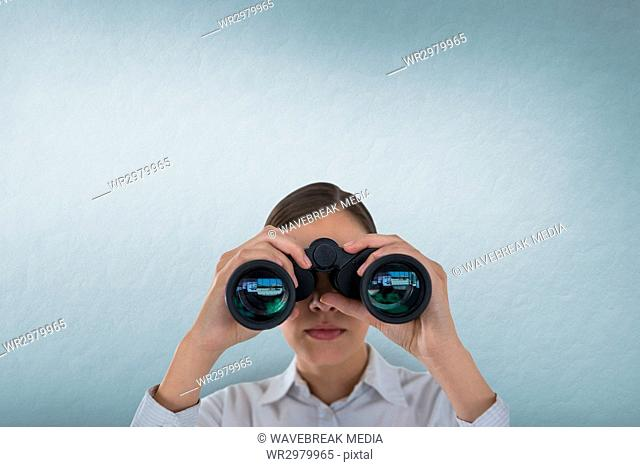 Woman looking through binoculars against white background