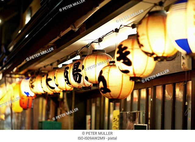 Row of illuminated paper lanterns at night, Tokyo, Japan