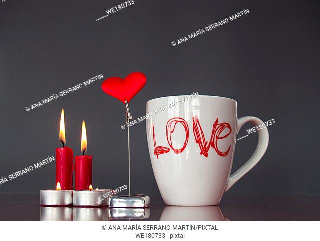 Concept of love Still life with red lit candles, a red heart and a breakfast cup with the word love