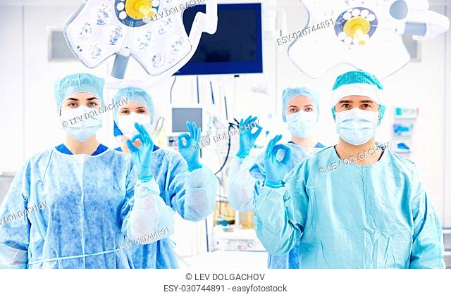 surgery, medicine and people concept - group of surgeons in operating, room at hospital