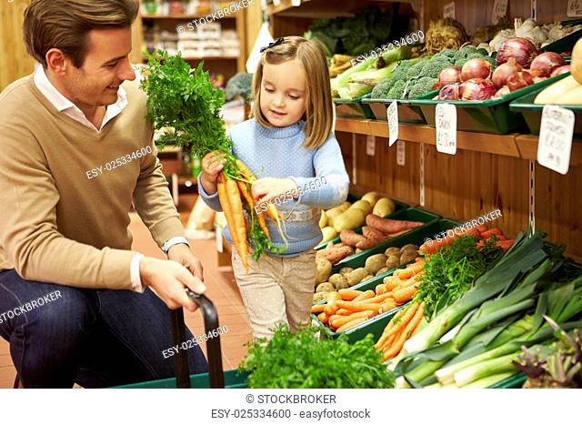 Father And Daughter Choosing Fresh Vegetables In Farm Shop
