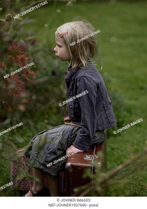 Girl sitting on suitcase, Varmdo, Uppland, Sweden
