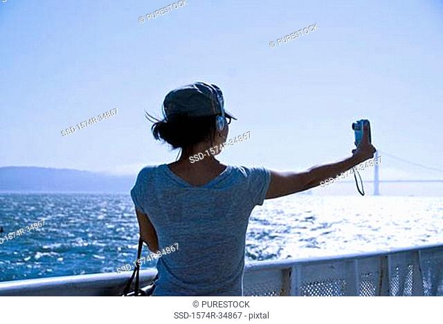 Rear view of a young woman taking a picture of herself with a digital camera, San Francisco, California, USA