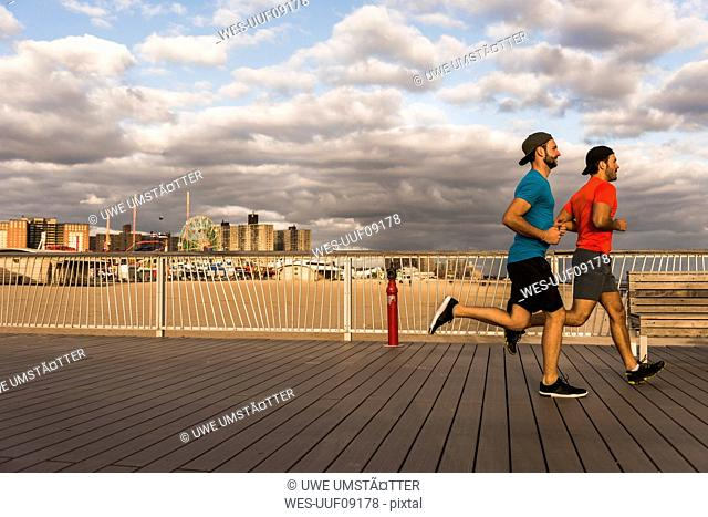 USA, New York City, two men running on Coney Island