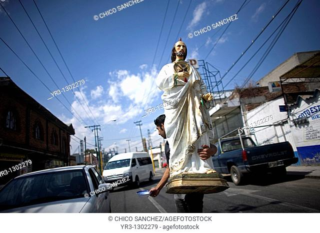 A man holds a sculpture of Saint Jude Thaddeus as he asks for charity in a street of Mexico City, February 15, 2010