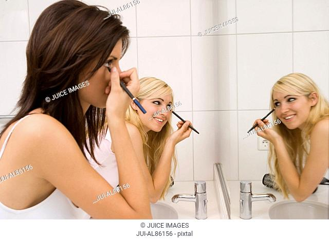 Two women putting on makeup in bathroom