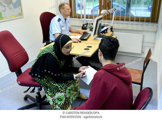 Interpreter Amine Rebmann (L) speaks to a refugee from Syria at the Federal police office in Flensburg, Germany, 6 August 2015