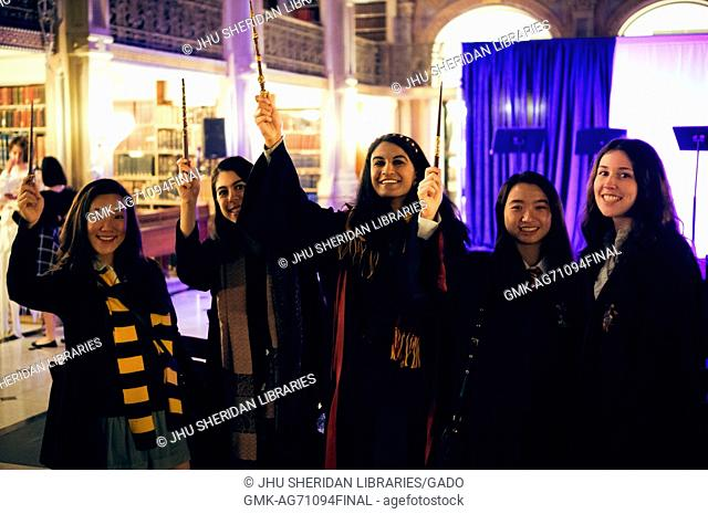 A group of college students pose for a picture, they are all wearing Harry Potter inspired outfits and are holding up their wands