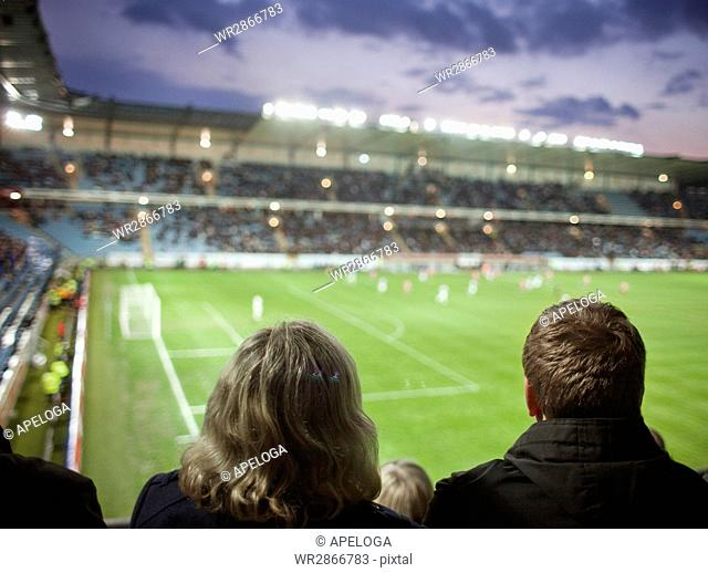 Rear view of people watching soccer match at stadium