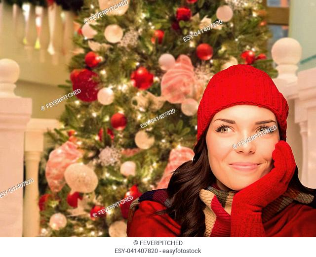 Warmly Dressed Female In Front of Decorated Christmas Tree