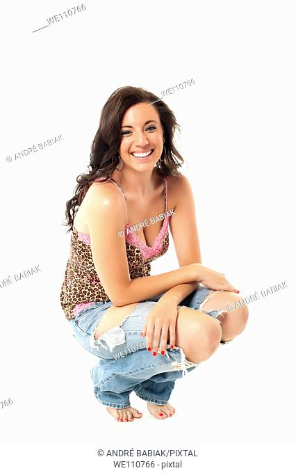 Teenage girl in torn jeans squatting