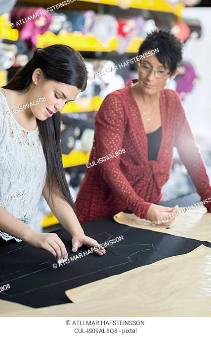 Two seamstresses chalking outline onto textile on work table