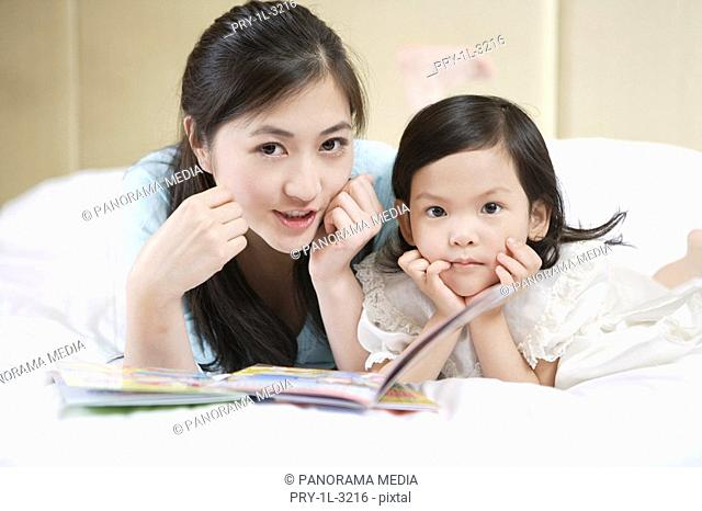 Young mother and daughter reading in bed