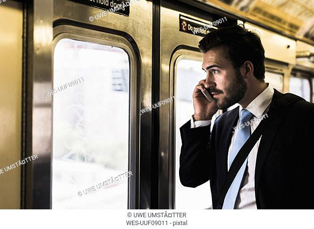 Young businessman taking metro, using smart phone