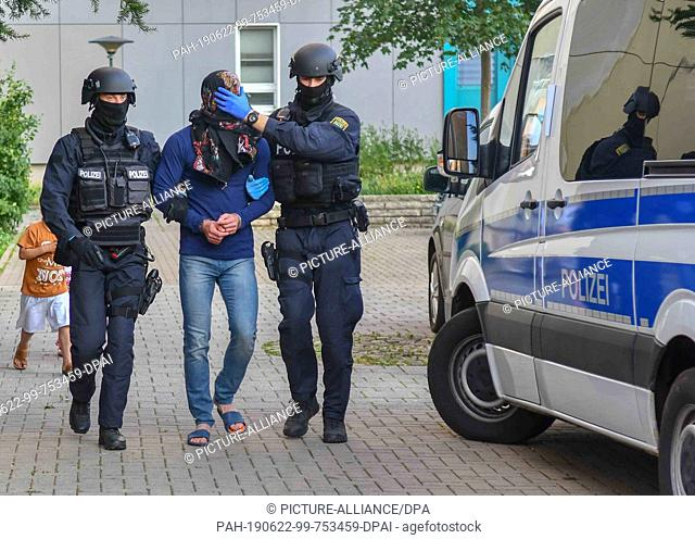 21 June 2019, Saxony-Anhalt, Magdeburg: Armed policemen take a man away during a drug raid. On Friday evening, the Special Operations Command (SEK) was deployed...