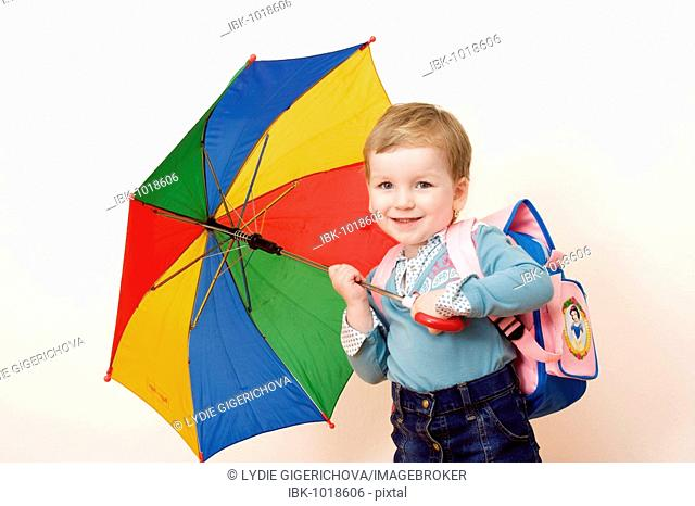 Little girl, 3 years, with umbrella and schoolbag