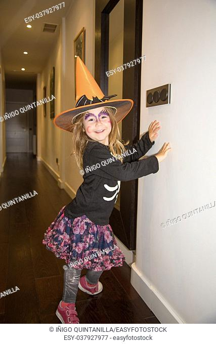 portrait of four years old blonde little girl in disguise for Halloween, with orange witch hat, black sweater and painted face, looking smiling face