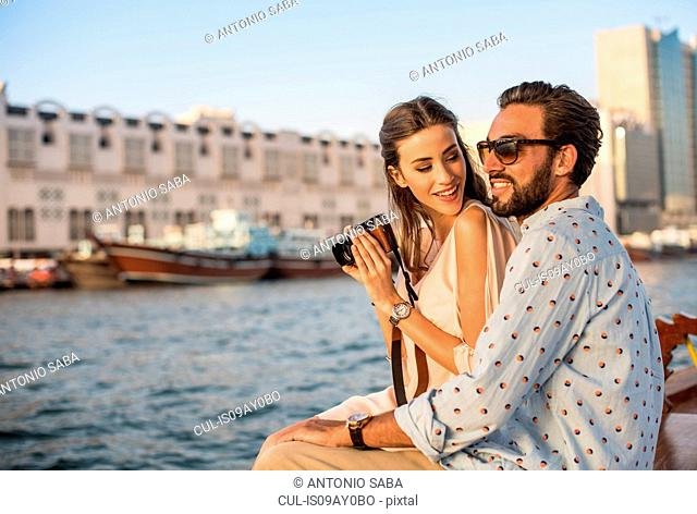 Romantic couple photographing on boat at Dubai marina, United Arab Emirates
