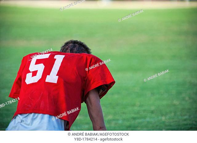 Back side of exhausted American football player without helmet