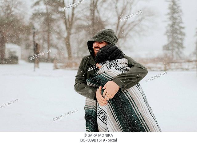 Couple wrapped in blanket in snowy landscape, Georgetown, Canada