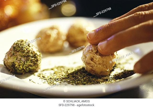 Rolling sausage forcemeat balls in crumbled herbs